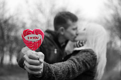 Couple kissing. Lollipop I love you. Black and white, partly color Stock Photography