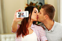 Couple kissing and making selfie photo on smarphone Stock Photography