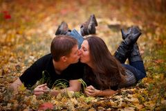Couple kissing in fall leaves Stock Photo