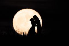 Couple Kissing in the Moon. A man and woman kiss in a silhouette against the moon Stock Images