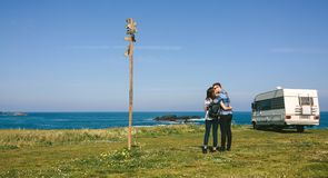 Couple kissing near the coast with a camper royalty free stock photo