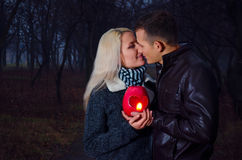 Couple kissing at night. Couple kissing in the park at night, holding in hands lantern heart Royalty Free Stock Photo