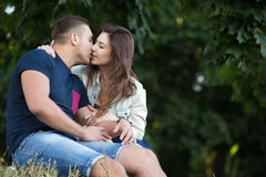 Couple kissing outdoors. Portrait of beautiful young couple in love wearing casual clothes gently kissing in park, sitting together on grass on summer day Stock Image