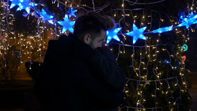 Couple kissing outside in a park near big Christmas Tree stock footage