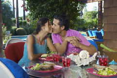 Couple Kissing Over Meal At Outdoor Table Stock Photo