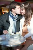 Couple kissing in a Parisian cafe Royalty Free Stock Photography