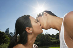 Couple Kissing In Park. Close-up of young couple kissing in park Stock Photos