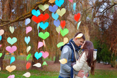 Couple kissing in the park, decoration background of hearts of p Stock Image