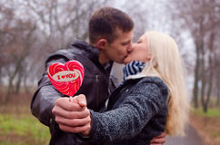 Couple kissing in the park. Holding in hands Lollipol I love you stock photo