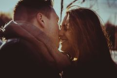 Couple kissing in the park at sunset. Photo in multicolor image style. Royalty Free Stock Photography