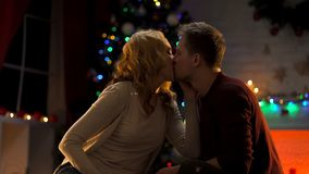 Couple kissing passionately under Christmas tree, holiday atmosphere, love royalty free stock photo