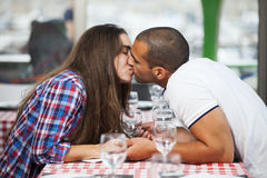 Couple kissing at the restaurant Stock Images