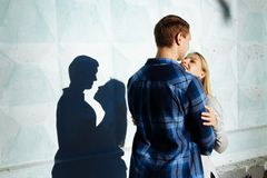 Couple Kissing Shadow.the shadow of a couple, between a man and a woman, kiss embracing. profile, silhouette. The shadow of a couple, between a men and a woman stock photos