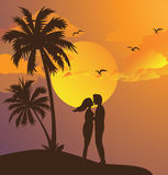 Couple kissing silhouette sunset on beach romantic moment yellow sky palm tree Royalty Free Stock Image