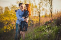 Couple kissing standing outdoos among bushes Stock Image
