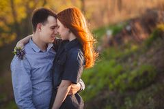 Couple kissing standing outdoos among bushes. Young couple kissing standing outdoos among bushes Stock Photography