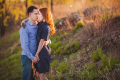 Couple kissing standing outdoos among bushes. Young couple kissing standing outdoos among bushes Royalty Free Stock Photo