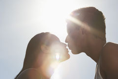 Couple Kissing In Sunlight. Close-up of young couple kissing in sunlight against sky Stock Photo