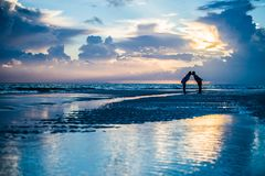 Couple kissing at sunrise on a beach royalty free stock image