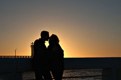 Couple kissing at sunset. Silhouetted couple kissing at sunset with harbor lighthouse in background Royalty Free Stock Photography