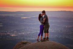 Couple kissing at sunset atop a mountain Stock Photo