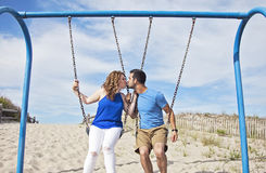 Couple kissing on swings Stock Photos