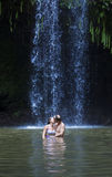 Couple kissing under a beautiful tropical waterfall. A couple embracing and kissing under a beautiful and picturesque tropical waterfall Stock Photo