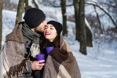 Couple kissing under plaid in winter park. Two young people dating in romantic snow atmosphere outdoors Royalty Free Stock Images