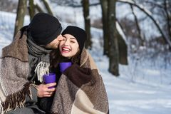 Couple kissing under plaid in winter park. Two young people dating in romantic snow atmosphere outdoors. Couple kissing under plaid in winter park Stock Photo