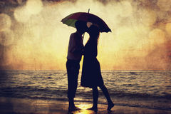 Couple Kissing Under Umbrella At The Beach In Sunset. Photo In O Stock Photography