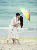 Couple kissing under umbrella at the beach Royalty Free Stock Photography
