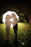 Couple kissing under the umbrella Stock Photos