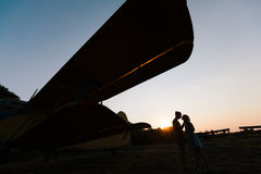 Couple is kissing under the vintage plane Royalty Free Stock Images