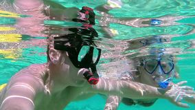 Couple kissing underwater. Beautiful playful couple underwater kissing in sea stock footage