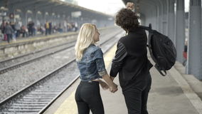 Couple kissing and walking hand in hand on railway station stock footage