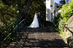 Couple Kissing After Wedding Near Stair Beside Garden Stock Photography