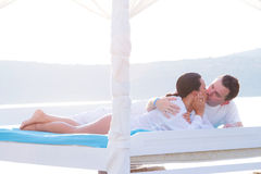 Couple kissing on white bed at the sea royalty free stock photos