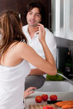 Couple in kitchen. Young couple in kitchen chatting each other royalty free stock images