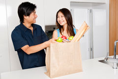 Couple In Kitchen. An attractive asian couple unpacking groceries in the kitchen at home royalty free stock photography