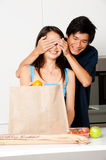 Couple In Kitchen. An attractive asian couple unpacking groceries in the kitchen at home royalty free stock images