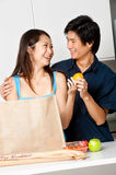 Couple In Kitchen. An attractive asian couple unpacking groceries in the kitchen at home royalty free stock photo