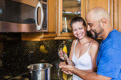 Couple at the kitchen. Wife gives husband a try on the food she is cooking Royalty Free Stock Image