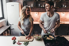 Couple on kitchen. Attractive couple is cooking on kitchen. Looking on each other and smiling Royalty Free Stock Photography