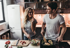 Couple on kitchen. Attractive couple is cooking on kitchen. Looking on each other and smiling Stock Image