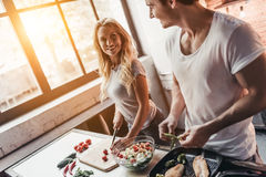 Couple on kitchen. Attractive couple is cooking on kitchen. Looking on each other and smiling Royalty Free Stock Image
