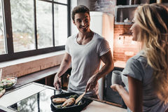 Couple on kitchen. Attractive couple is cooking on kitchen. Looking on each other and smiling Stock Photo