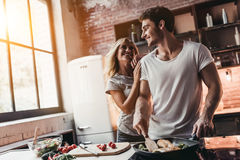 Couple on kitchen. Attractive couple is cooking on kitchen. Looking on each other and smiling Stock Photos