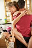Couple In Kitchen Being Interrupted Daughter. Romantic Couple Hugging In Kitchen Being Interrupted By Daughter Stock Images