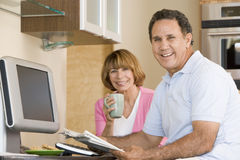 Couple in kitchen with coffee and newspaper Royalty Free Stock Photos