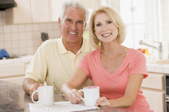 Couple in kitchen with coffee smiling royalty free stock photo